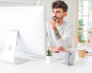 young tattooed professional on computer