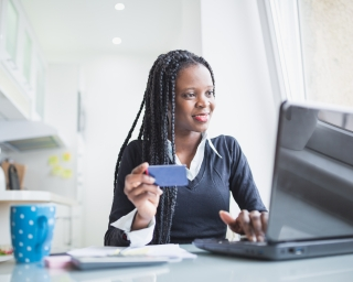 African American woman at computer with credit card