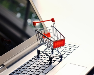 Miniature shopping cart on a laptop keyboard.